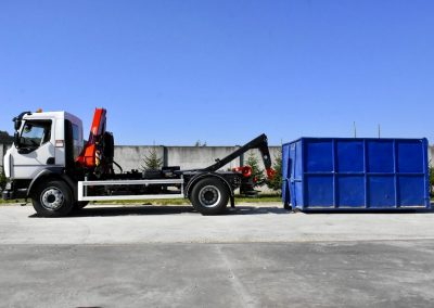 Nákladné auto s hydraulickou rukou a hákovým nosičom kontajnerov.